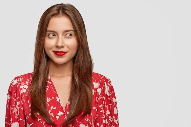 Aantrekkelijke jonge europese vrouw met lang donker haar, rood geverfde lippen en stijlvolle blouse, kijkt peinzend opzij, heeft een dromerige uitdrukking, staat tegen een witte muur met kopie ruimte aan de linkerkant