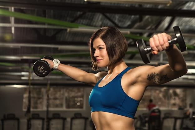 Aantrekkelijke jonge fit en afgezwakt sportvrouw doet laterale verhoogt vertrouwen vol vertrouwen