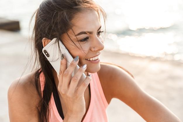 Aantrekkelijke jonge fitness vrouw met behulp van mobiele telefoon tijdens het rusten op het strand na het joggen, praten