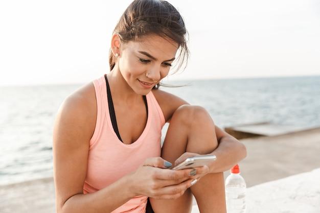 Aantrekkelijke jonge fitness vrouw met behulp van mobiele telefoon tijdens het rusten op het strand na het joggen