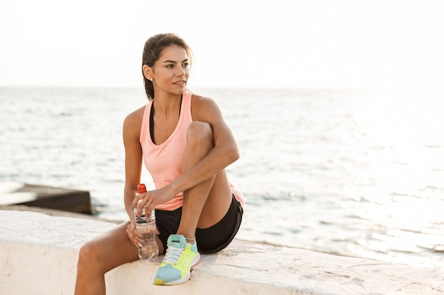 Aantrekkelijke jonge fitness vrouw rusten op het strand na het joggen, waterfles te houden