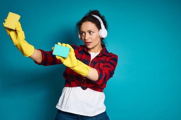 Aantrekkelijke jonge gemengde rasvrouw die met hoofdtelefoons schoonmakende sponzen houden en het wassen van een onzichtbaar oppervlak simuleren