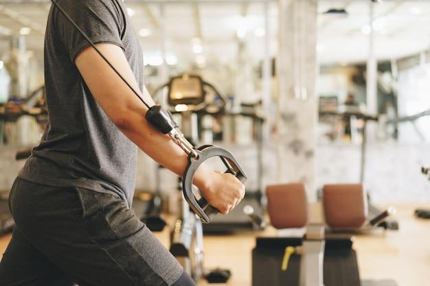 Aantrekkelijke jonge gescheurde bodybuilder die in gymnastiek uitwerkt.