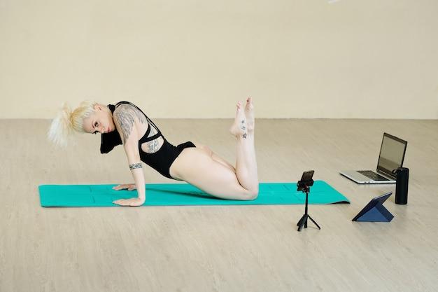 Aantrekkelijke jonge geschikte vrouw die filmt die sensuele dans in studio uitvoert