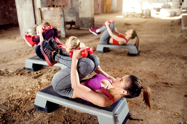 Aantrekkelijke jonge geschiktheidsvrouwen die oefeningen doen bij de oude verlaten hangaar.