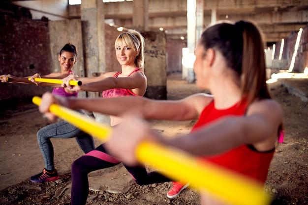 Aantrekkelijke jonge geschiktheidsvrouwen die oefeningen doen bij de oude verlaten schuilplaats.