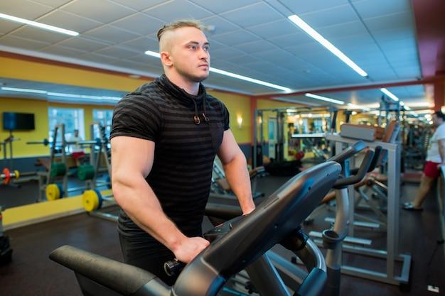 Aantrekkelijke jonge gespierde man tijdens het hardlopen op een loopband in de sportschool