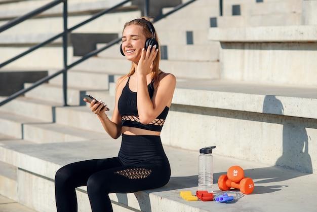 Aantrekkelijke jonge gezonde sportvrouw luistert naar muziek met koptelefoon tijdens de training in het stadion.