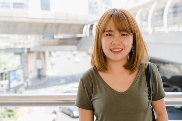 Aantrekkelijke jonge glimlachende aziatische vrouw buitenshuis portret in de stad
