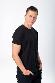 Aantrekkelijke jonge glimlachende mens die een zwart katoenen t-shirt met korte mouwen en zwarte jeans draagt die in studio stellen. studio die op een witte achtergrond is ontsproten.