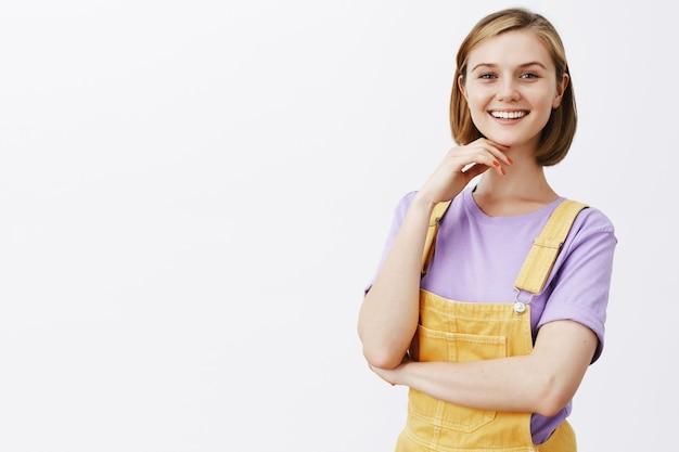 Aantrekkelijke jonge glimlachende vrouw die in de zomerkleren tevreden en gelukkige, witte muur kijkt