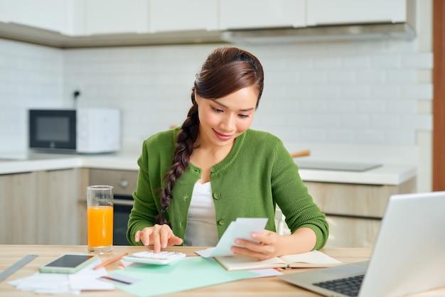 Aantrekkelijke jonge glimlachende vrouw die rekeningen online betaalt met behulp van laptop vanuit huis zittend in de keuken
