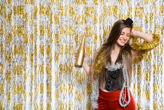 Aantrekkelijke jonge glimlachende vrouw in avondkleding met fles drank