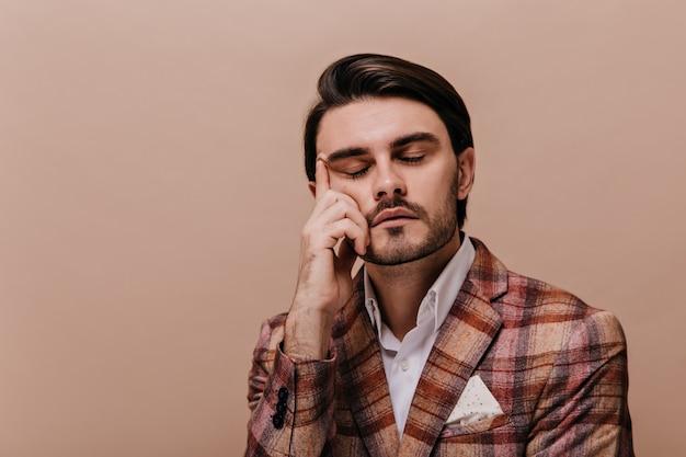 Aantrekkelijke jonge heer met gesloten ogen, donkerbruin haar en borstelharen, met een wit overhemd en een donkere warme jas die tegen een beige muur poseert en het gezicht met één hand aanraakt