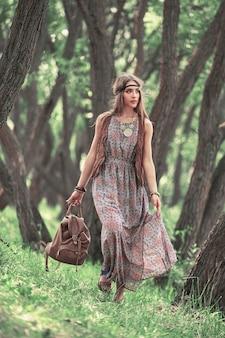 Aantrekkelijke jonge hippievrouw die onder bomen in bos loopt