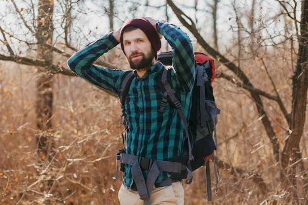 Aantrekkelijke jonge hipster man reizen met rugzak in herfst bos dragen geruit overhemd en hoed, actieve toerist, natuur in koude seizoen verkennen