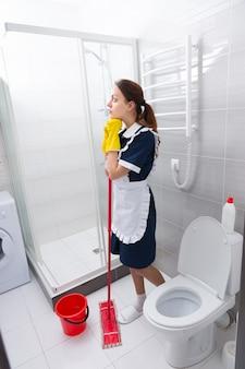 Aantrekkelijke jonge huishoudster die staat te dagdromen terwijl ze op haar dweil leunt terwijl ze de vloer in een badkamer schoonmaakt
