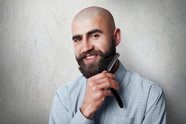 Aantrekkelijke jonge kale kapper met dikke zwarte baard en snor die lacht terwijl hij een scheermes op zijn baard houdt