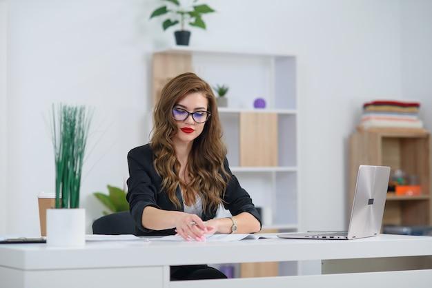 Aantrekkelijke jonge kantoorvrouw in formele kleding werkt met zakelijk papierwerk aan de balie.