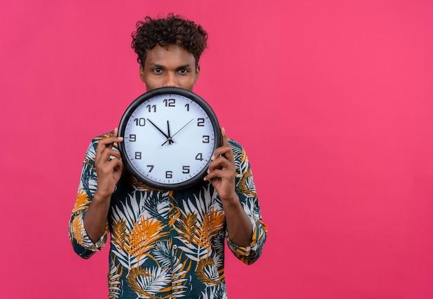 Aantrekkelijke jonge knappe donkere man met krullend haar in bladeren gedrukt shirt met wandklok met tijd