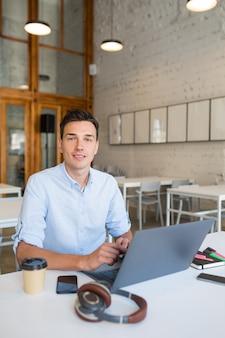 Aantrekkelijke jonge knappe lachende man zit in open ruimte kantoor die op laptop werkt