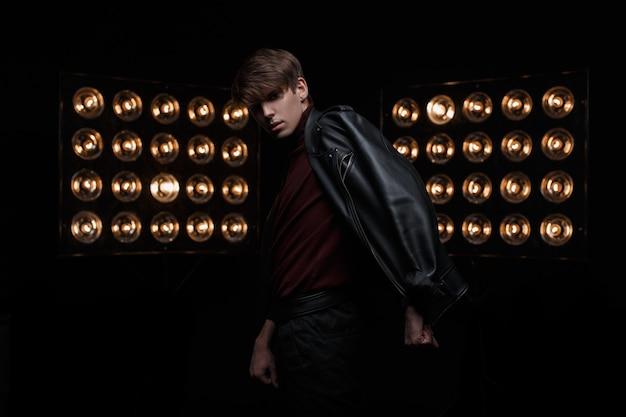 Aantrekkelijke jonge knappe man met modieus kapsel in een zwarte stijlvolle jas in bourgondische golf en trendy jeans vormt in een donkere studio in de buurt van een heldere vintage professionele lampen. mooi ventmodel