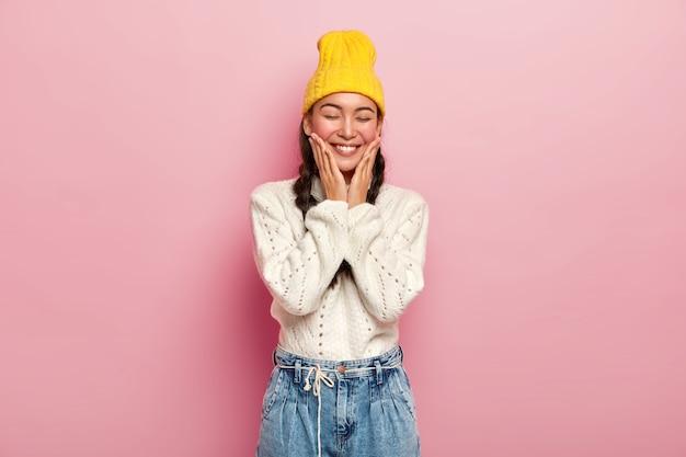Aantrekkelijke jonge koreaanse vrouw raakt wangen, heeft tevreden uitdrukking, houdt de ogen dicht, voelt zich verlegen, draagt gele hoed en gebreide trui