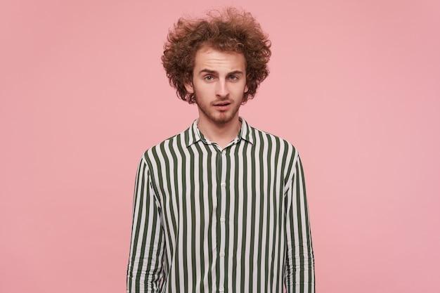 Aantrekkelijke jonge krullende roodharige man met casual kapsel handen naar beneden houden terwijl poseren over roze muur, camera kijken met kalm gezicht en rimpelend voorhoofd