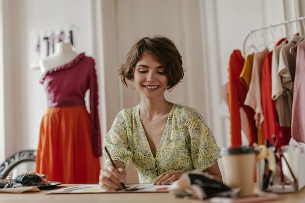 Aantrekkelijke jonge krullende vrouw in stijlvolle v-hals bloemenjurk glimlacht oprecht, houdt pen vast en poseert in het kantoor van modeontwerper