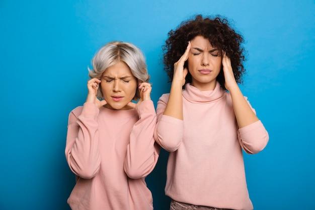 Aantrekkelijke jonge krullende vrouw met haar vrouwelijke beste vriend die hun hoofd met allebei raakt omdat het hebben van hoofdpijn op blauwe muur wordt geïsoleerd.