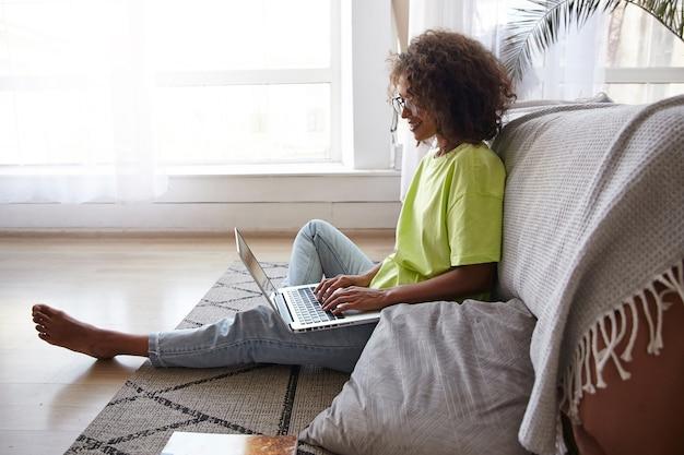 Aantrekkelijke jonge krullende vrouw zittend op de vloer met laptop, handen houden op toetsenbord en scherm kijken, spijkerbroek en geel t-shirt dragen