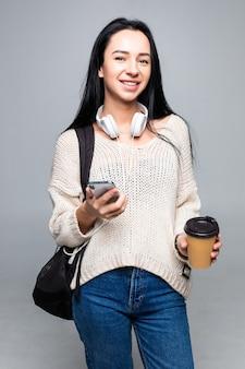 Aantrekkelijke jonge leuke donkerbruine vrouw terwijl het gebruiken van slimme telefoon en het drinken van koffie die op grijze muur wordt geïsoleerd