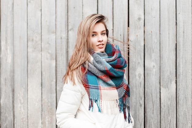Aantrekkelijke jonge leuke vrouw in een stijlvolle witte warme jas met een wollen modieuze warme kleurrijke sjaal staande op straat in de buurt van de houten vintage muur. meisje met mooie blauwe ogen