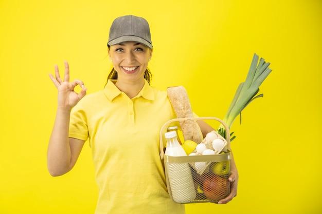 Aantrekkelijke jonge leveringsvrouw die en ok teken glimlacht toont