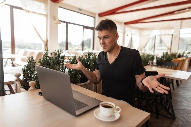 Aantrekkelijke jonge man blogger in een zwart t-shirt zit in een café kijkt naar een laptop en spreekt zijn verbazing uit.