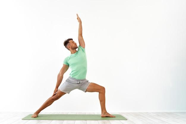 Aantrekkelijke jonge man die geavanceerde yoga beoefent op wit een reeks yogahoudingen voor goed hij...