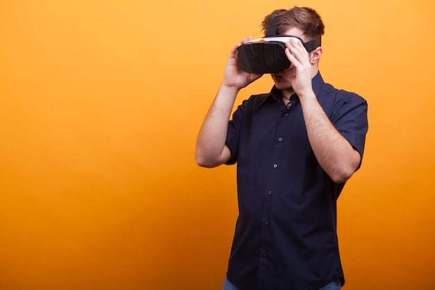 Aantrekkelijke jonge man die het fantastisch heeft met zijn vr-headset over gele achtergrond. virtuele realiteit verkennen