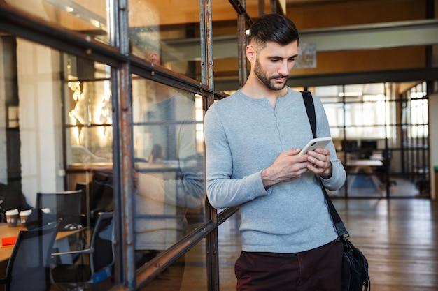 Aantrekkelijke jonge man die in de hub staat, met behulp van mobiele telefoon