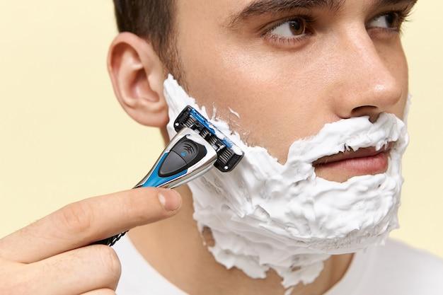Aantrekkelijke jonge man die vóór het werk scheert die wegwerpscheermes houdt om zijn gezicht te scheren met behulp van schuim