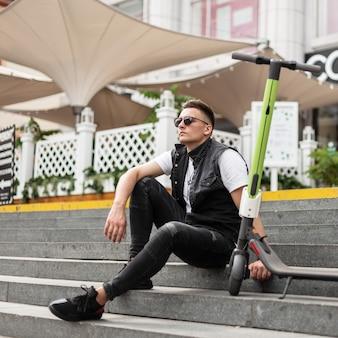 Aantrekkelijke jonge man hipster in trendy zwarte jeans kleding in zonnebril zit naast een elektrische scooter