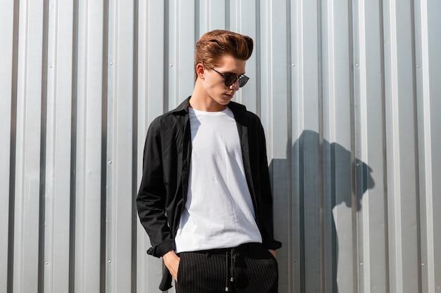 Aantrekkelijke jonge man hipster met een stijlvol kapsel in een t-shirt in een elegant zwart shirt in zonnebril rusten in de buurt van metalen wand in de stad. modieuze kerel die op straat ontspant. trendy herenkleding.
