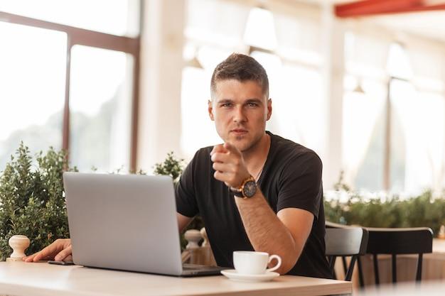 Aantrekkelijke jonge man in een stijlvol zwart t-shirt wijst met een vinger naar de camera. succesvolle man freelancer werkt op een laptop op internet zittend in een café. afstandswerk.