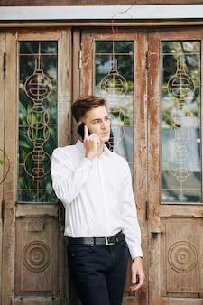 Aantrekkelijke jonge man in een wit overhemd praten over de telefoon als hij buiten staat