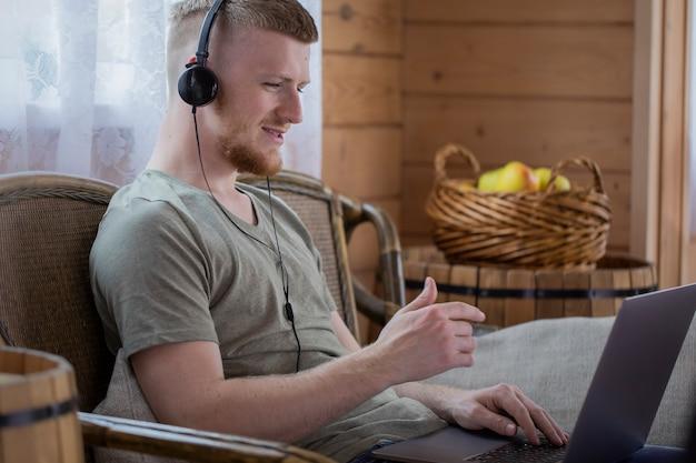 Aantrekkelijke jonge man in koptelefoon werkt met laptop, communiceert in sociale netwerken