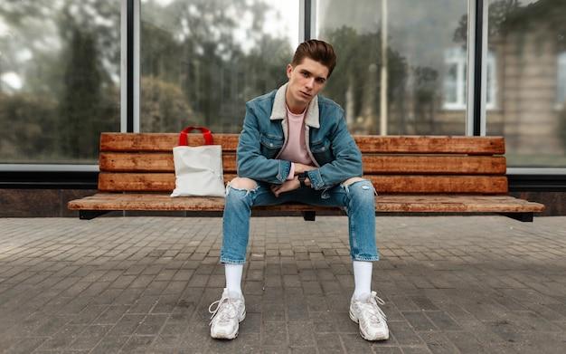 Aantrekkelijke jonge man in modieuze blauwe jeugd jeans kleding in witte stijlvolle sneakers met vintage stoffen tas zit op houten bankje bij bushalte in de stad. knappe trendy man in jeans dragen rust op straat