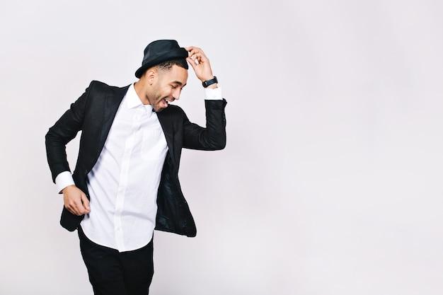 Aantrekkelijke jonge man in pak dansen, plezier maken. stijlvolle vooruitzichten, hoed, succesvolle zakenman, blij, echte positieve emoties uiten, grappig.