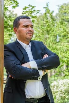 Aantrekkelijke jonge man in pak staat met zijn armen gekruist over zijn borst