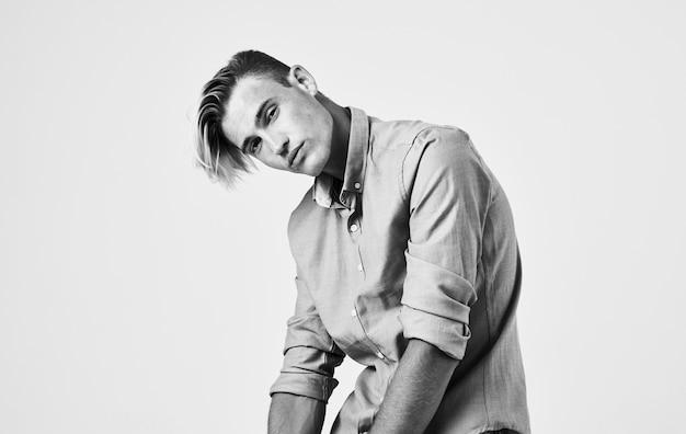 Aantrekkelijke jonge man in shirt en broek op een licht zwart-wit fotografie portret.
