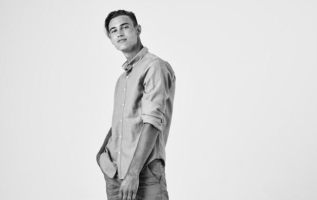 Aantrekkelijke jonge man in shirt en broek op een lichte achtergrond zwart-wit fotografie portret. hoge kwaliteit foto