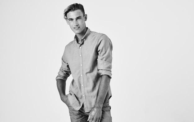 Aantrekkelijke jonge man in shirt en broek op een lichte zwart-wit fotografie